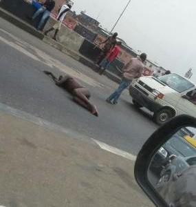 Photos: man strips naked, lies on the road causing traffic in Lagos