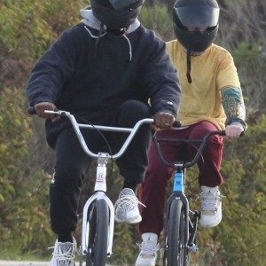 Kanye West flashes his wedding ring as he goes on a bike ride with pals