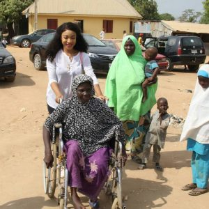 Tonto Dikeh carries crippled woman during visit to physically challenged people in Abuja